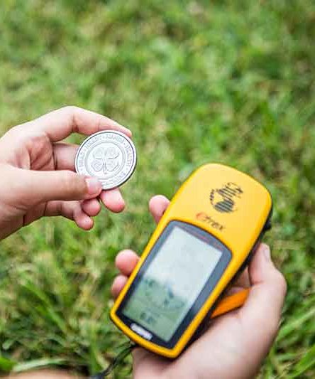 Image of a child holding a 4-H logo on a coin and a Garmin GPS navigator