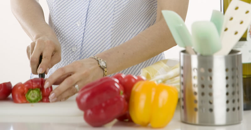 Woman cutting peppers in kitchen